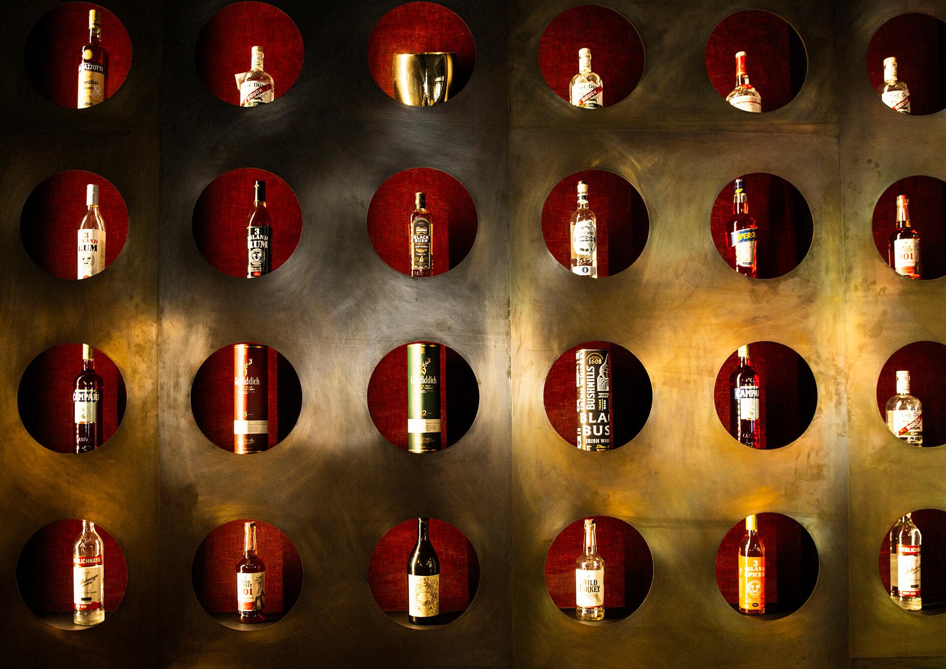 Regal mit schallplattengroßen Löchern dient als Auslage für Hochprozentiges in der 33rpm Bar im Jams